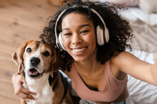 Young African Woman In Casual Wear With Beagle Puppy