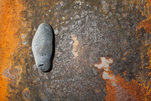 Small Pebble Lying On Rusty Steel, Abstract, Background.