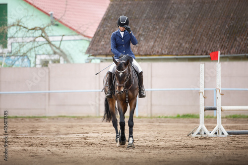 beautiful woman rider on horse greets during equestrian showjumping competition Poster Mural XXL