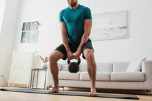 Cropped View Of Barefoot Man Lifting Kettlebell At Home