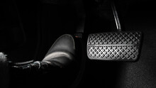 Foot Pressing Foot Pedal Of A Car To Drive. Accelerator And Brake Pedal In A Car. Driver Driving The Car By Pushing Accelerator And Break Pedals Of The Car. Inside Vehicle. Control Pedal. Close Up.