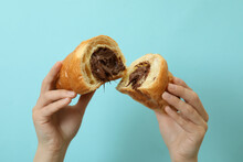 Female Hands Holds Croissant With Chocolate On Blue Background