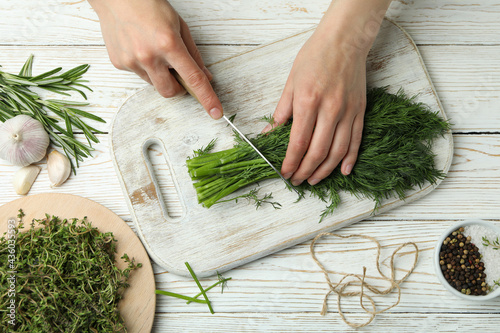 Fotografering Female hands cuts dill on white wooden background, top view