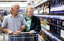 Mature Couple Chooses Bottle Of Wine In Alcohol Section Of Supermarket