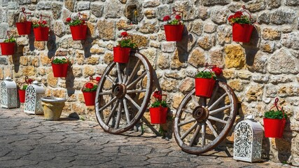 Czerwone doniczki z kwiatami na kamiennym murze w greckim miasteczku