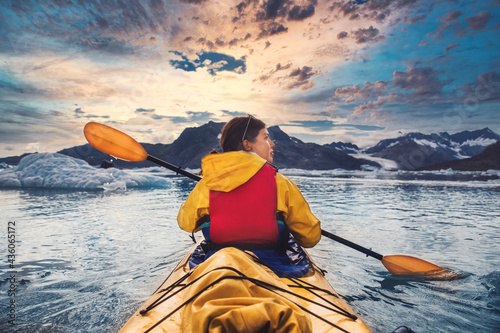 Fotomural Woman paddle a canoe on an icy bay in Alaska exploring glaciers