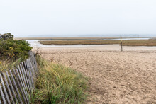 View Of Coastal Marsh On A Foggy Autumn Morning. A Weathered Fence At The Foot Of Grassy Sand Dunes Is In In Foreground. Sandwich, Cape Cod, MA, USA.