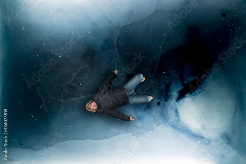Dark blue ice sheet depicting a frozen arctic ocean surface, with a man laying o Fototapet