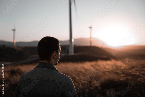 Man watching the sunset surrounded by windmills Fototapet