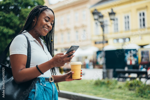 Canvastavla Cheerful african american woman using smartphone and drinking coffee takeaway ou