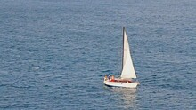 Small Single Masted Sailing Ship Underway In Bosphorus Sea. Sail Yacht Under Full Sail Out Of Istanbul Offshore