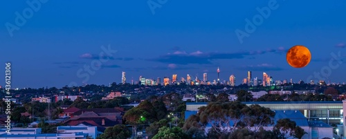 Obraz na płótnie Large orange moon rising behind Sydney CBD buildings NSW Australia