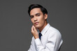 Portrait of smart handsome Asian man in corporate wear touching face in light gray isolated studio background