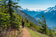 Person Hiking On A Trail On Elk Mountain, British Columbia On A Sunny Day With Snow Capped Mountains In The Background