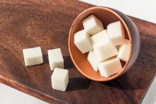 In A Clay Bowl, Lumpy Sweet White Sugar On A Wooden Board.