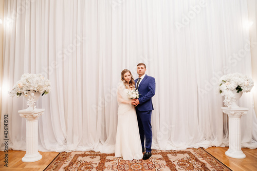 Canvas beautiful and happy bride and groom against the background of the white curtain