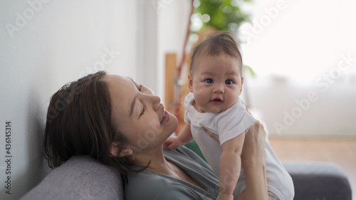 Fotografie, Obraz asian woman mother holding happy baby infant playing and kissing on sofa in living room at minimal style home in day time