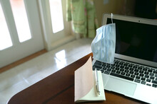 Work From Home During Lockdown. Selective Focus On Face Mask Hanging On Laptop, With Notepad On Table.
