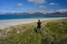 Man Gazing Out Over White Sands And Turquoise Water Of Luskentyre Beach In Isle Of Harris, Outer Hebrides, Scotland. Mountains In Background.