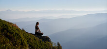 Fit Young Woman Sitting On Grassy Hill In Lotus Position And Doing Gyan Mudra Hand Gesture While Mediating Outdoors. Sporty Woman Doing Meditation Yoga Exercise In Mountains. Copy Space.
