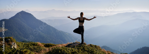 Fotografie, Obraz Back view of woman practicing yoga in evening mountains