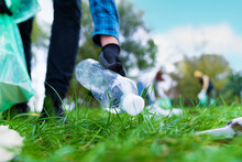 Hand Of Man Picking Up Bottle Into Garbage Bags While Cleaning Area In Park. Volunteering, Charity, People, Ecology Concept. Closeup Volunteer Collecting Plastic Trash In Forest. World Clean Up M Day