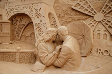 A Sculpture Of Lovers Made Of Sand Against The Backdrop Of The Eiffel Tower. Parisian Mood.