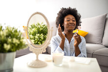 Woman Using Rose Quartz Roller On Her Face At Home. Happy Curly Young Woman Is Doing Face Massage With Cosmetology Gadget Before Mirror In Living Room At Home