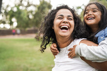Happy Indian Mother Having Fun With Her Daughter Outdoor - Family People And Love Concept - Focus On Mum Face