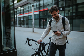 Happy cyclist in the city using phone
