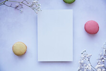 Mock Up Of Stationery Card On Purple Vintage Surface With Bright Colorful Macaroons, Gypsophila. Happy Holidays Or Present Card Concept. Top View. Feminine Concept