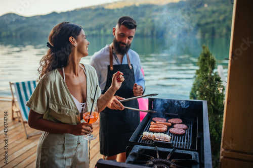 Couple grilling food at barbecue outdoors
