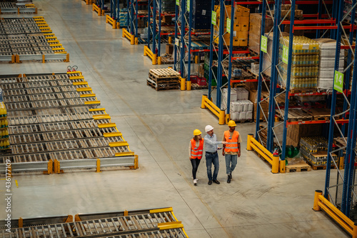 Warehouse employees walking through shelves and talking