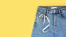 Measuring Tape And Jeans On A Bright Yellow Background. Weight Loss Concept By Summer
