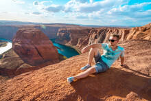 Panoramic View Of A Young Woman Sitting On The Edge Of A Cliff Facing The Horseshoe Bend, A Horseshoe Meander Of The Colorado River In The Town Of Page, Arizona