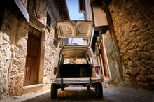 Wide Angle Rear View White Historic Vehicle With Open Trunk On Narrow Cobblestone Street In A Village