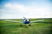 Walking Small Propeller Plane On A Green Field