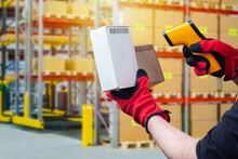 A Person Reads Barcodes From Cardboard Boxes. A Person Collects Orders For An Online Store. Work Of A Picker In A Warehouse.