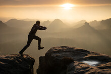 Jumping Over The Summit Ridge Of A Peaks At Sunset. Man Takes Leap Of Faith Off Of Rock Outcropping