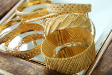 Gold Bracelets Studio Shoot. Gold Jewelry And Gems Concept.