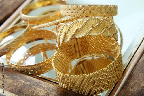 Papel de parede Gold bracelets studio shoot. Gold jewelry and gems concept.