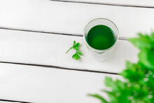 Top View Of Chlorophyll Water In A Glass On White Wooden Table With Copy Space