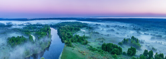 Smoky morning mist over the river. Beautiful panoramic view of river and green banks of the river in the early summer morning.