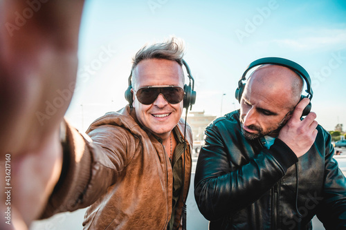 Obraz na plátně Disc jockeys having fun doing selfie while playing music for tourist people at c