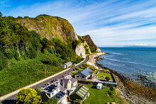 Northern Ireland, UK. Atlantic Coast With Cliffs,  Cliffs And Coastal Road Called Causeway Coastal Route At Garron Point. One Of The Most Scenic Coastal Roads In Europe. Small Village. Aerial View