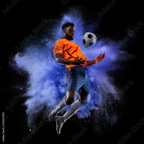 One young sportsman soccer football player in explosion of colored neon powder isolated on dark background
