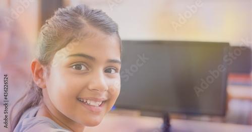 Composition of orange glow over happy school girl using computer