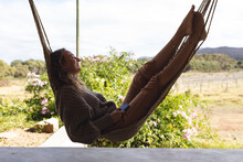 Smiling Caucasian Woman Lying In Hammock On Sunny Cottage Terrace, Looking To Garden