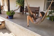 Happy Caucasian Woman Relaxing In Hammock On Cottage Terrace, Using Tablet