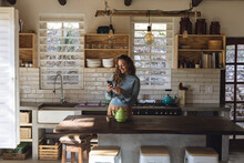Happy Caucasian Woman Standing In Cottage Kitchen Using Smartphone And Smiling